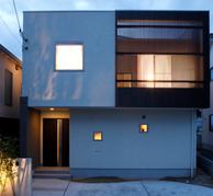 白で仕上げた外壁に木調格子のアクセントの四角いおうち